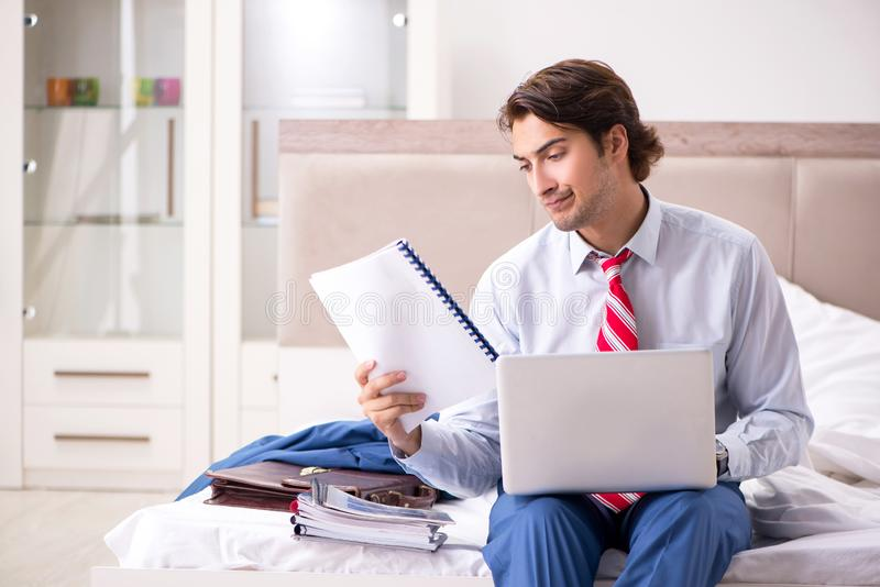 The young employee working at home sitting on the bed. Young employee working at home sitting on the bed royalty free stock photo