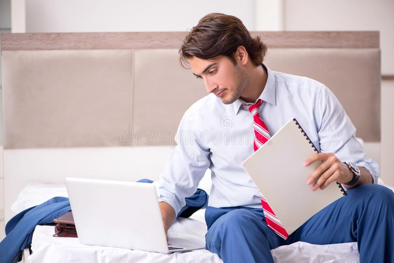 The young employee working at home sitting on the bed. Young employee working at home sitting on the bed royalty free stock photos