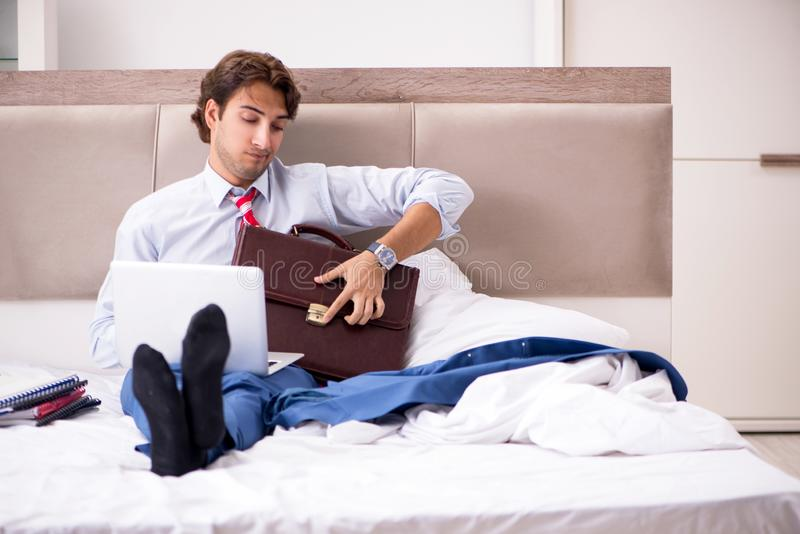 The young employee working at home sitting on the bed. Young employee working at home sitting on the bed stock photography