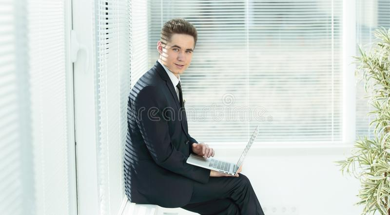 Young employee working on a laptop sitting in the corridor of the office. Photo with copy space royalty free stock images