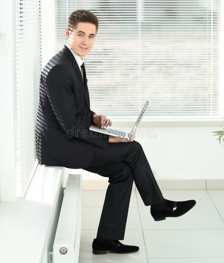 Young employee working on a laptop sitting in the corridor of the office. Photo with copy space royalty free stock image