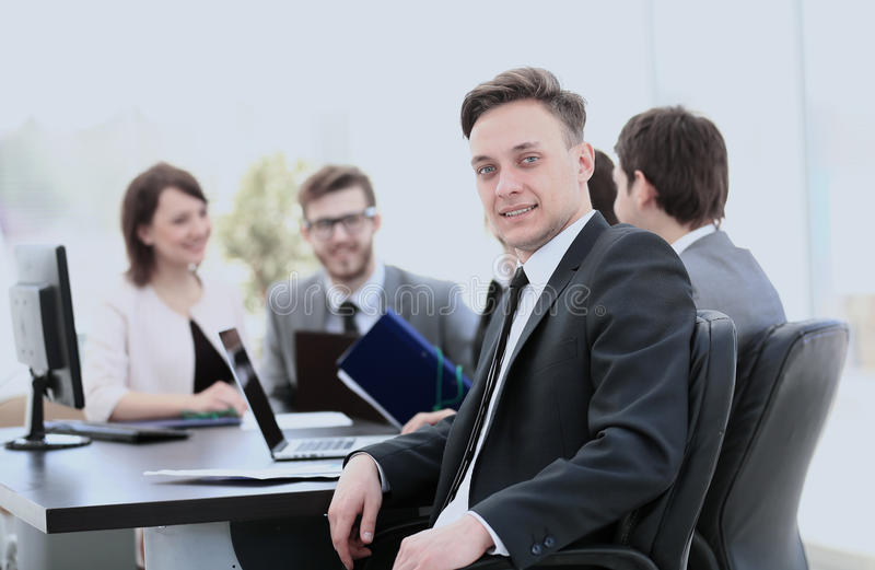 young employee in the workplace and the business team in the bac royalty free stock photography