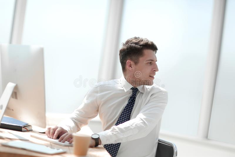 Young employee in the workplace in the office stock image