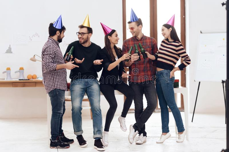 Young employees of the company celebrate a corporate holiday. They put on holiday caps and have fun stock images