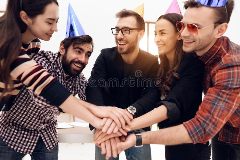 Young employees of the company celebrate a corporate holiday. They put on holiday caps and have fun royalty free stock photo