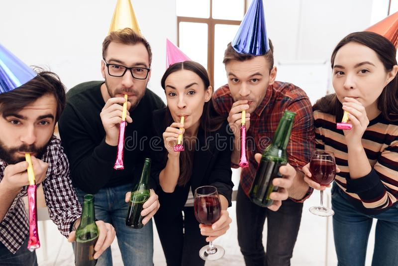 Young employees of the company celebrate a corporate holiday. They put on holiday caps and have fun royalty free stock images