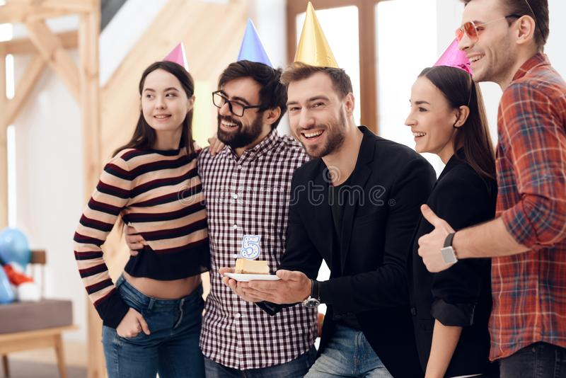 Young employees of the company celebrate a corporate holiday. They put on holiday caps and have fun royalty free stock photography