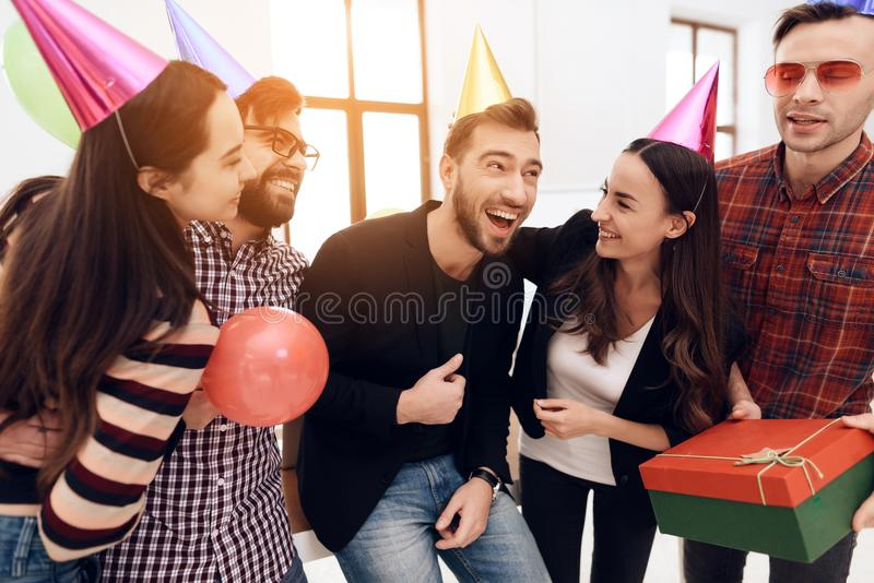 Young employees of the company celebrate a corporate holiday. They put on holiday caps and have fun stock photography