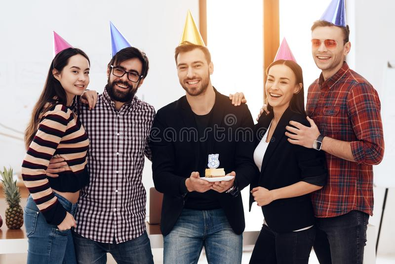 Young employees of the company celebrate a corporate holiday. They put on holiday caps and have fun stock photos