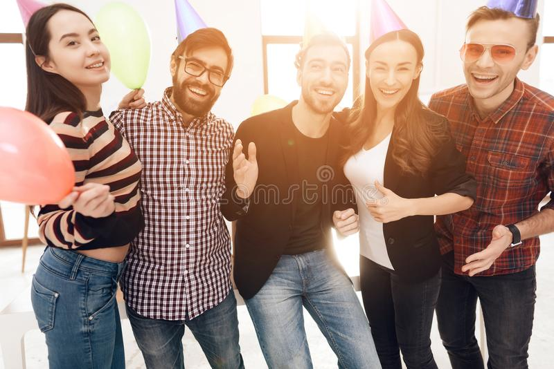 Young employees of the company celebrate a corporate holiday. They put on holiday caps and have fun royalty free stock image