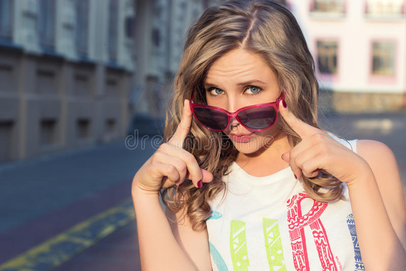Young energetic, happy girl in red sunglasses in the city on a Sunny day royalty free stock photo