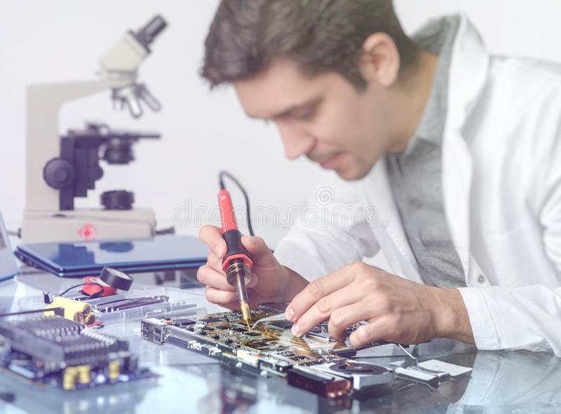 Young energetic male tech or engineer repairs electronic equipment. Electronics background. Young energetic male tech or engineer repairs electronic equipment in royalty free stock image