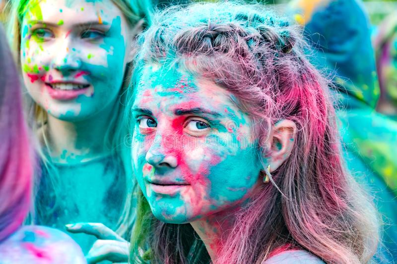 Young energetic teenagers at the festival of paints of holi in Russia. royalty free stock images