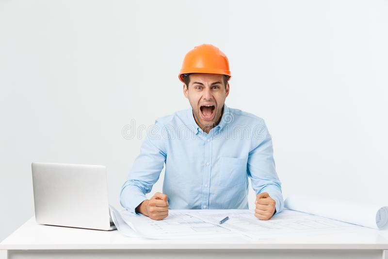 Young Engineer angry during working with laptop in office building site, he has problems with his new project manager stock photos