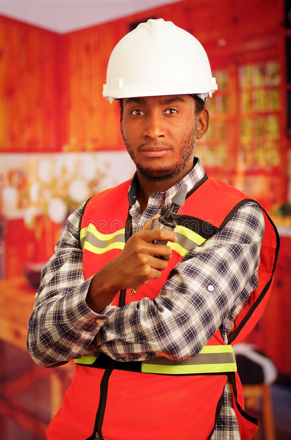Young engineer carpenter wearing helmet, square pattern flanel shirt with red safety vest, holding small handheld. Electric polisher tool smiling to camera royalty free stock photography