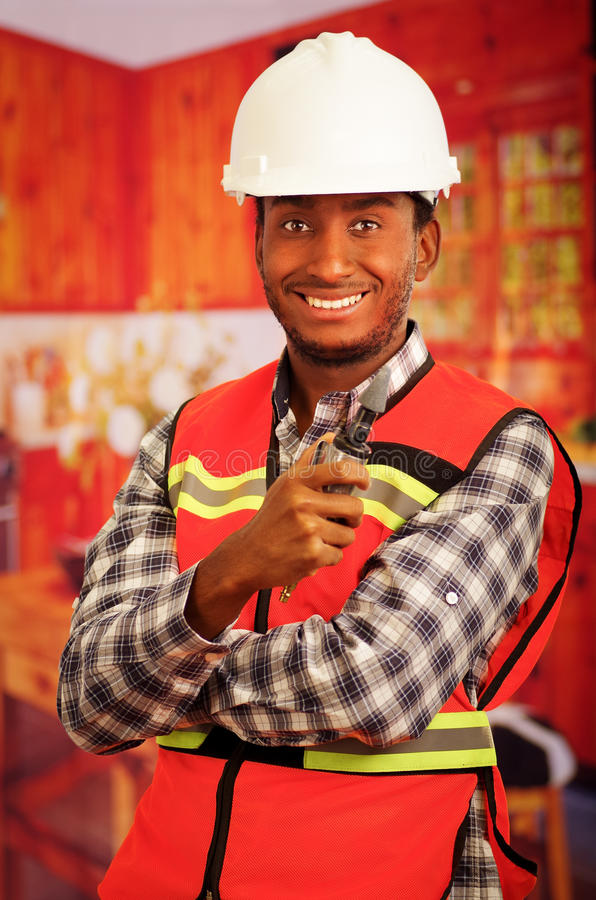 Young engineer carpenter wearing helmet, square pattern flanel shirt with red safety vest, holding small handheld. Electric polisher tool smiling to camera stock photos