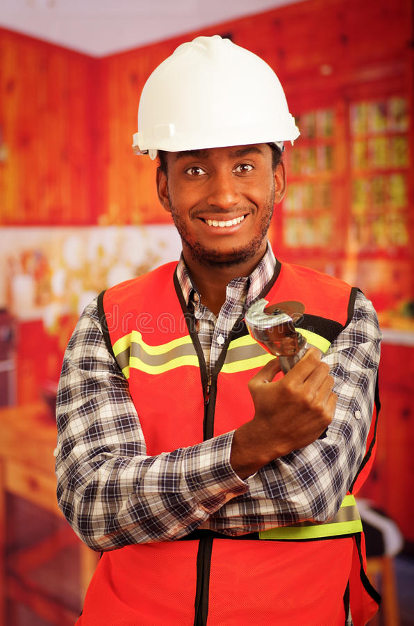 Young engineer carpenter wearing helmet, square pattern flanel shirt with red safety vest, holding small handheld. Electric saw smiling to camera stock photos