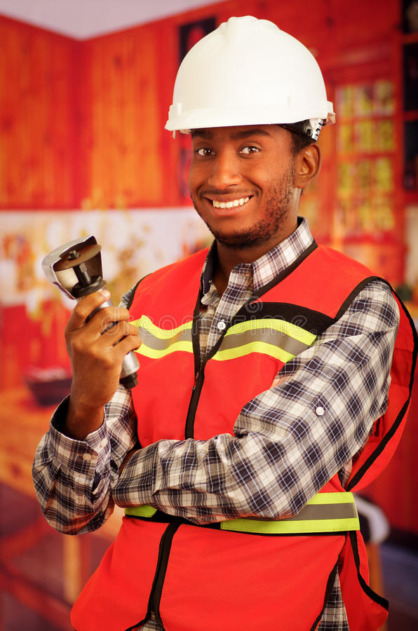 Young engineer carpenter wearing helmet, square pattern flanel shirt with red safety vest, holding small handheld. Electric saw smiling to camera royalty free stock photo