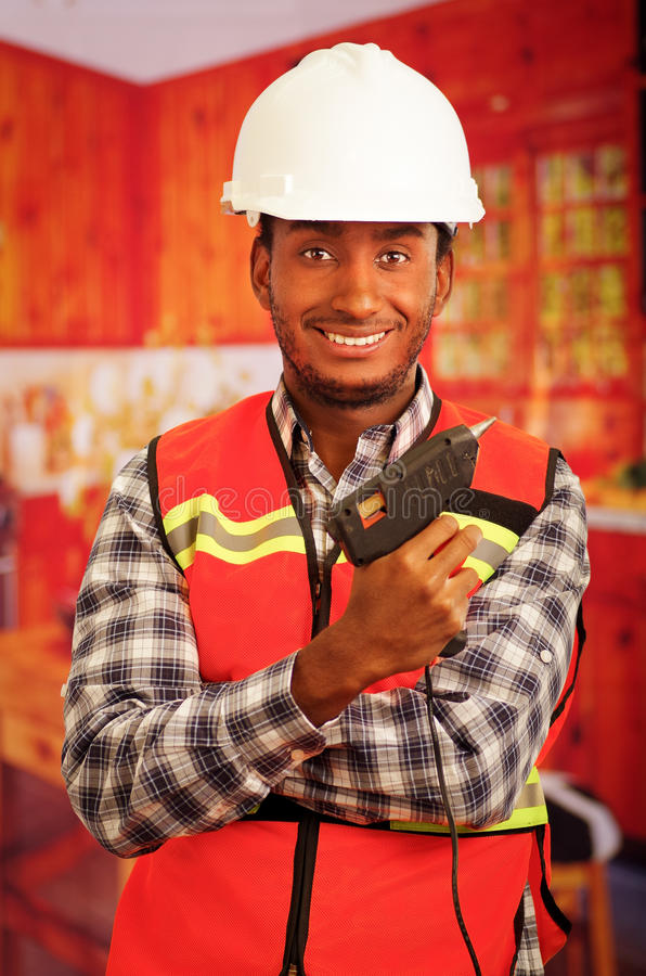Young engineer carpenter wearing square pattern flanel shirt with red safety vest, holding glue gun smiling to camera.  stock images