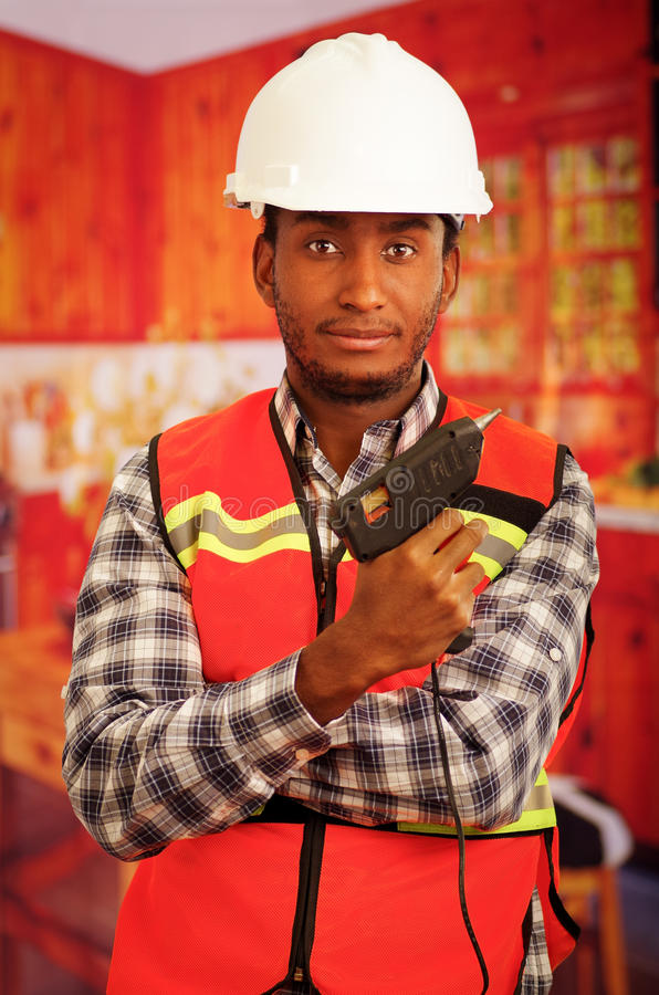 Young engineer carpenter wearing square pattern flanel shirt with red safety vest, holding glue gun smiling to camera.  stock image