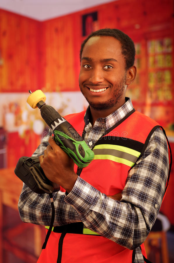 Young engineer carpenter wearing square pattern flanel shirt with red safety vest, holding handheld electric power drill. Smiling to camera stock photography