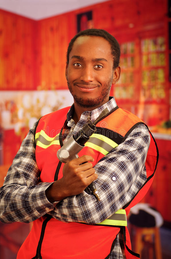 Young engineer carpenter wearing square pattern flanel shirt with red safety vest, holding handheld electric power tool. Smiling to camera stock photos