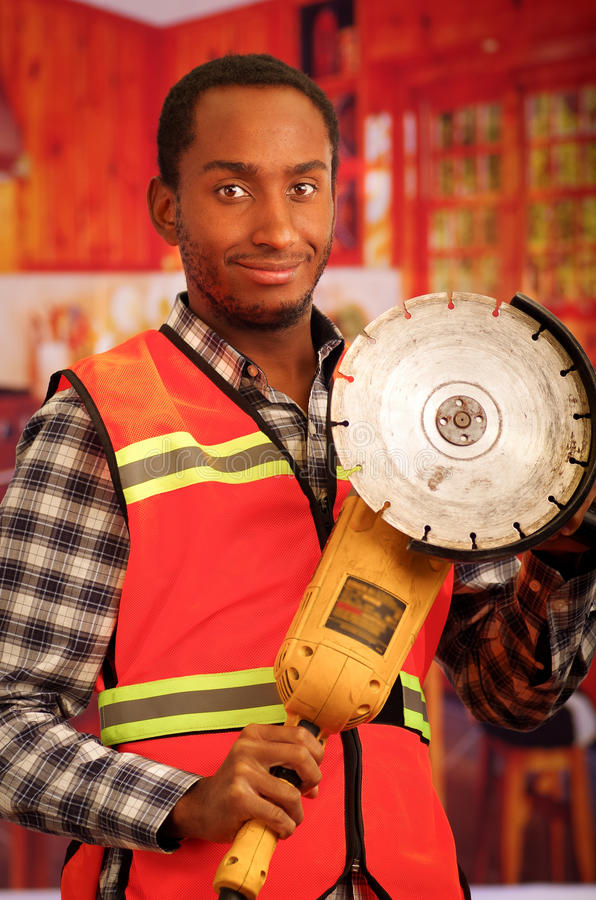 Young engineer carpenter wearing square pattern flanel shirt with red safety vest, holding handheld electric sander tool. Smiling to camera royalty free stock photography