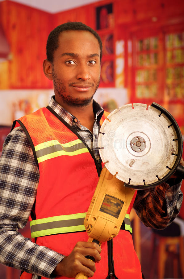 Young engineer carpenter wearing square pattern flanel shirt with red safety vest, holding handheld electric sander tool. Smiling to camera stock photos