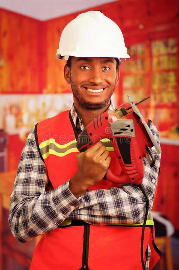 Young engineer carpenter wearing square pattern flanel shirt with red safety vest, holding jigsaw smiling to camera.  royalty free stock image