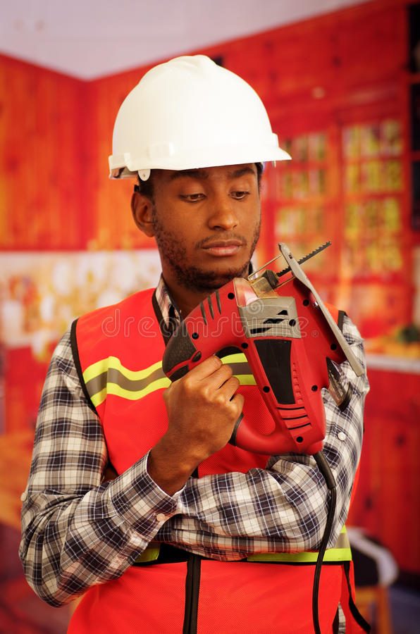 Young engineer carpenter wearing square pattern flanel shirt with red safety vest, holding jigsaw smiling to camera.  royalty free stock photo