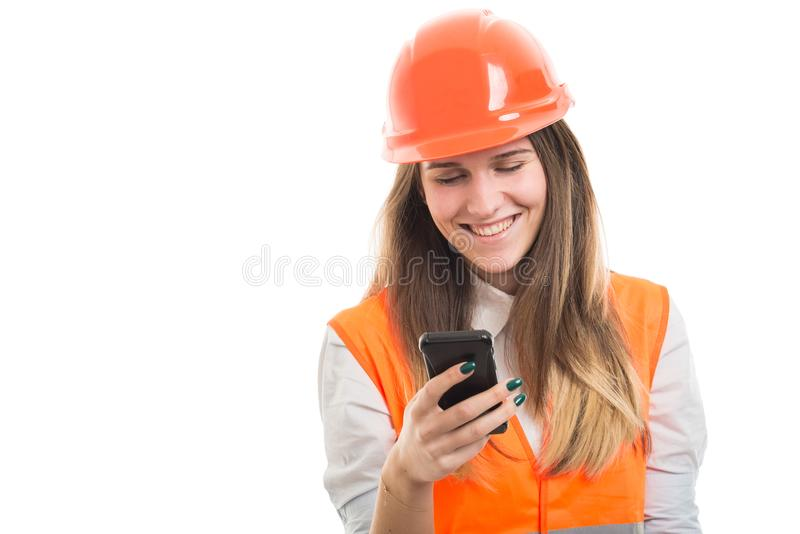Young engineer girl reading messages on smartphone royalty free stock photos
