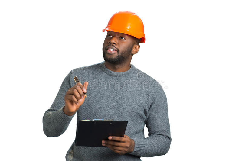 Young engineer inspecting construction. Handsome afro american architect with clipboard close up. Attractive project manager with helmet and clipboard on white royalty free stock photos