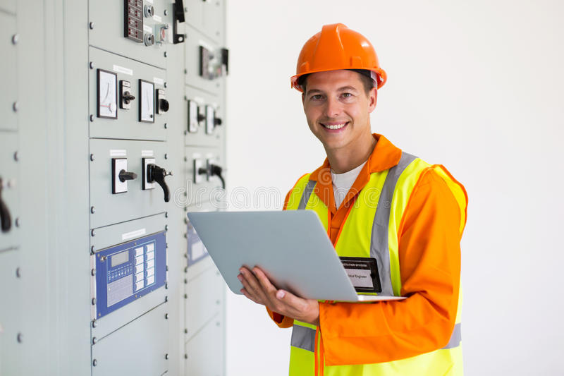 Young engineer laptop. Portrait of young engineer with laptop in control room stock photo