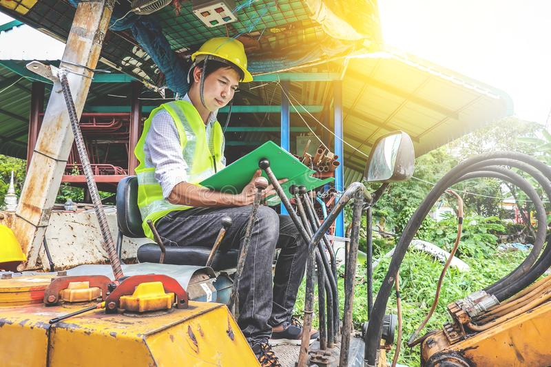 Young engineer man Hold the file and inspect the document in excavator at construction site stock photos