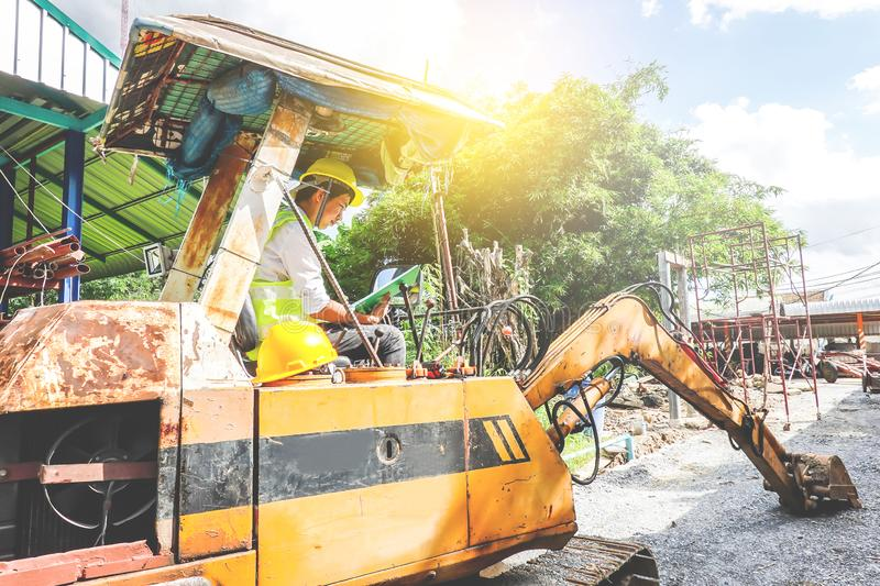 Young engineer man Hold the file and inspect the document in excavator at construction site stock images