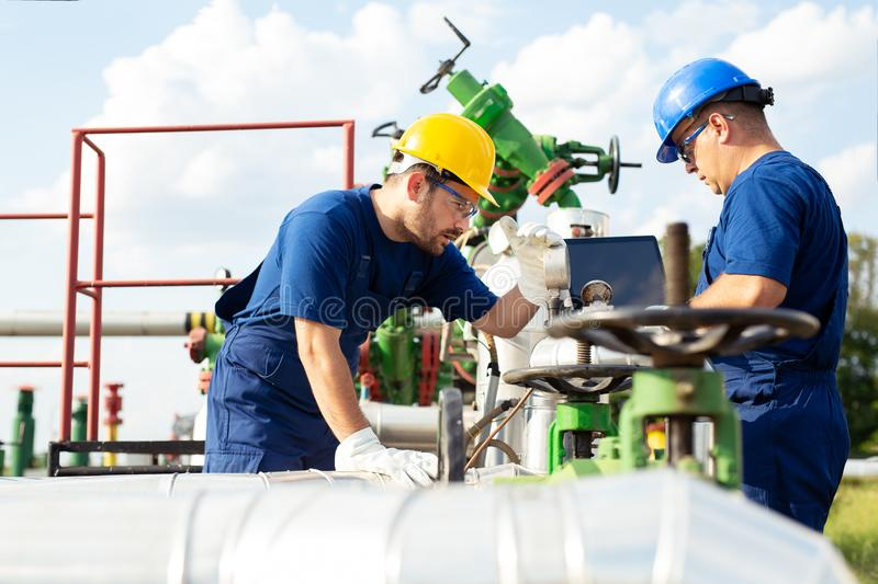 Two engineers working inside oil and gas refinery. Young Engineer power and energy using laptop on location site stock image