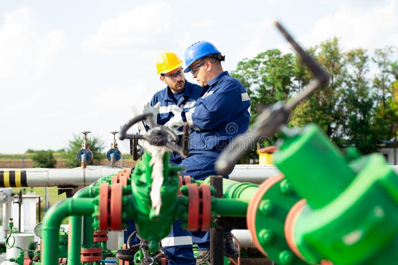 Two engineers working inside oil and gas refinery. Young Engineer power and energy using laptop on location site royalty free stock photography