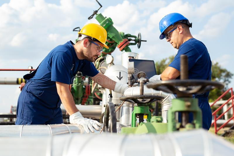 Two engineers working inside oil and gas refinery. Young Engineer power and energy using laptop on location site royalty free stock images