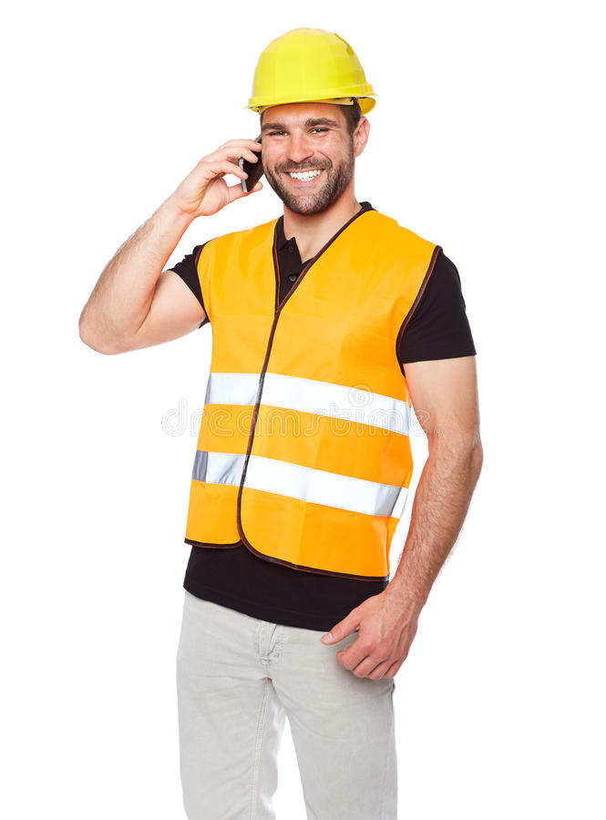Young engineer in a reflective vest with phone in hand. Young engineer in a reflective vest with yellow helmet calling by phone royalty free stock photo