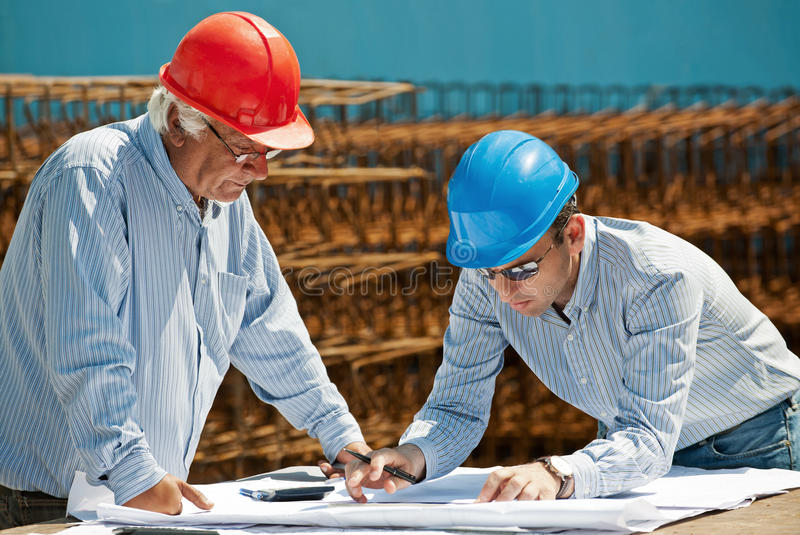 Young engineer and senior foreman stock photos