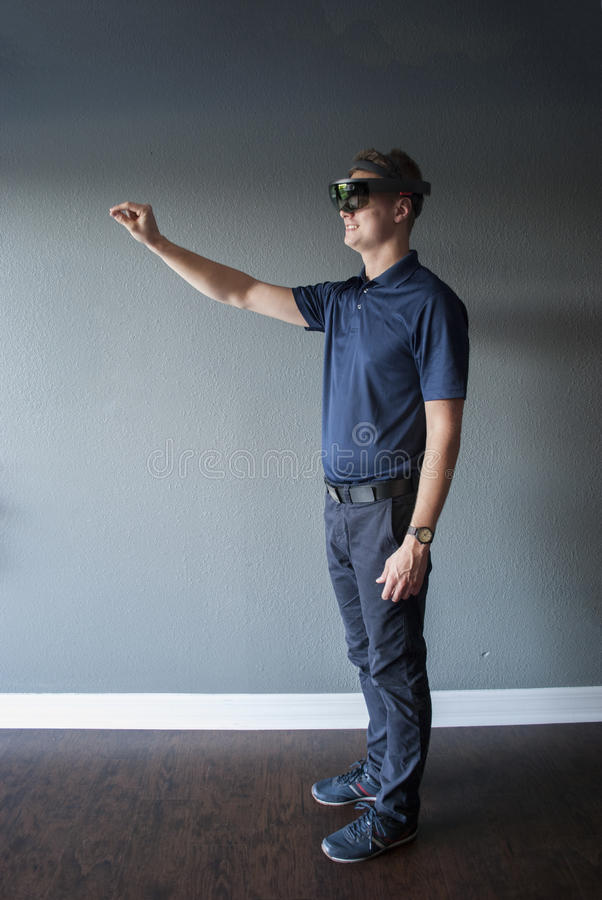 Young engineer showing special gesture for mixing real surrounding and virtual reality. Smiling young man with hologram headset showing how to create a virtual stock image