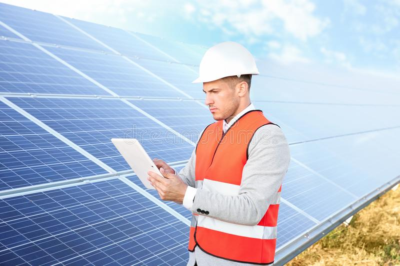 Young engineer with tablet computer standing near solar panels stock photo