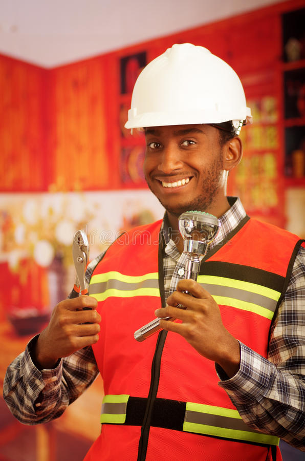 Young engineer wearing square pattern flanel shirt with red safety vest, holding showerhead and pliars smiling to camera.  royalty free stock images