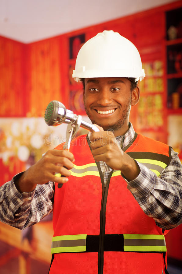 Young engineer wearing square pattern flanel shirt with red safety vest, holding showerhead and pliars smiling to camera.  royalty free stock photos