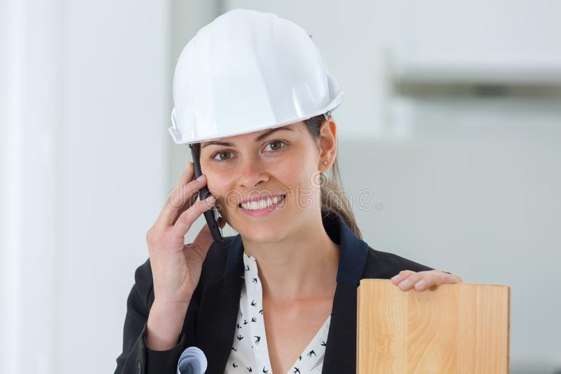 Young engineer woman with safety hard hat talking on phone royalty free stock image