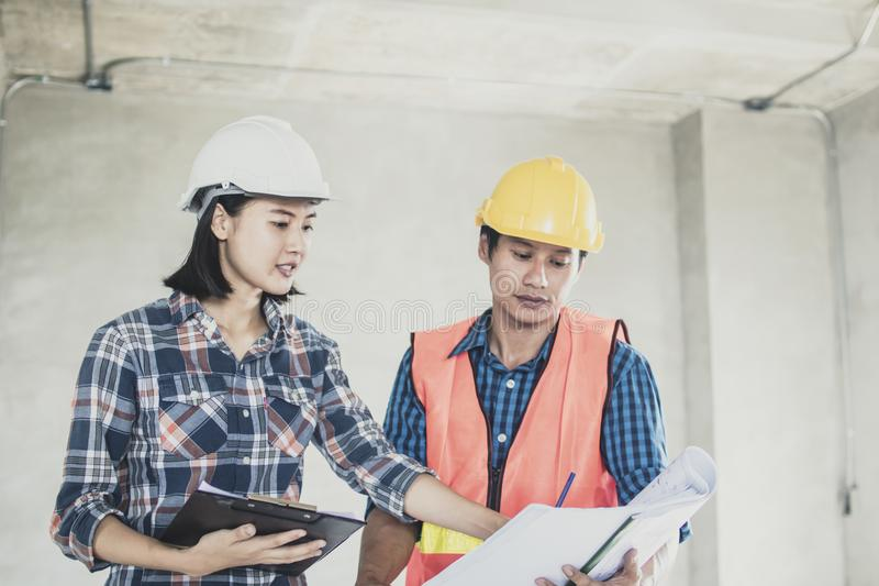Young engineer women and worker looking at blueprint and planning the construction indoor working site royalty free stock image