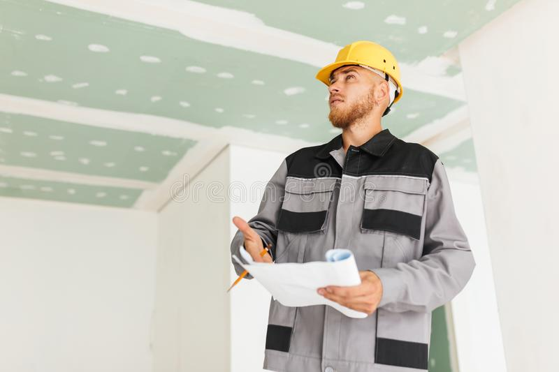 Young engineer in work clothes and yellow hardhat holding plan o. F new apartment in hand thoughtfully looking aside at work royalty free stock photos