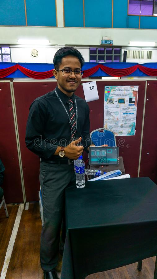Young engineering student presenting his product named I-BOX at the Final Year Project exhibition. Bangi, Malaysia - November 13, 2019: Young engineering student royalty free stock image