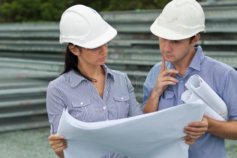 Young engineers solving a problem on site royalty free stock photo