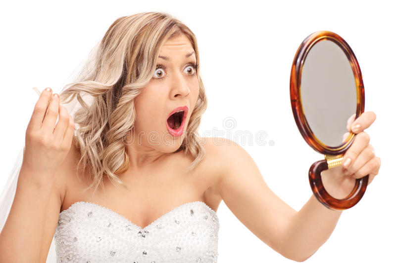Young enraged bride looking at her hairstyle. In a mirror isolated on white background stock photo